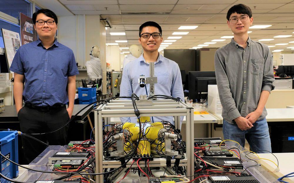Investigadores junto a la bobina electromagnética que permite el movimiento de los robots. (Foto NTU Singapore)